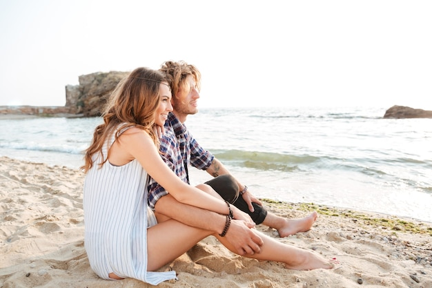 Beau jeune couple assis sur la plage en été
