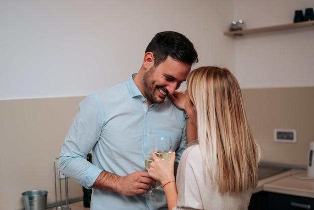 Beau jeune couple boit du vin et des caresses en se tenant debout.