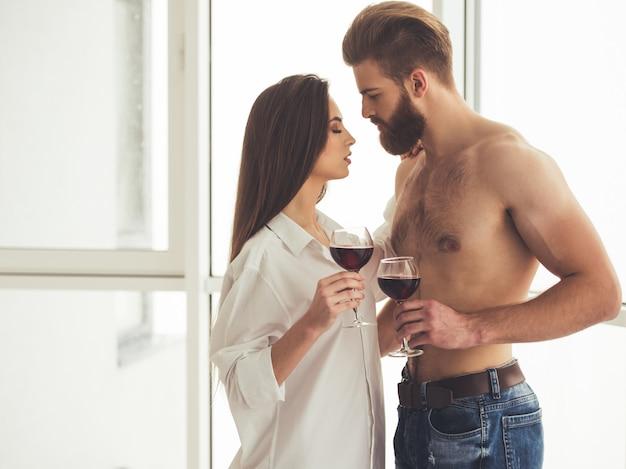 Beau jeune couple boit du vin et étreint.