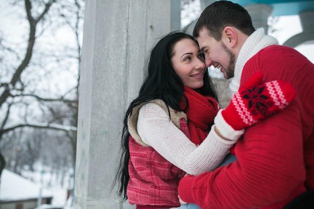 Beau jeune couple câliné en forêt d'hiver
