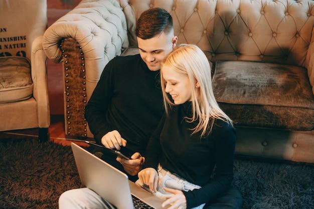 Beau jeune couple caucasien assis sur le sol de près et riant tout en regardant un écran d'ordinateur portable.