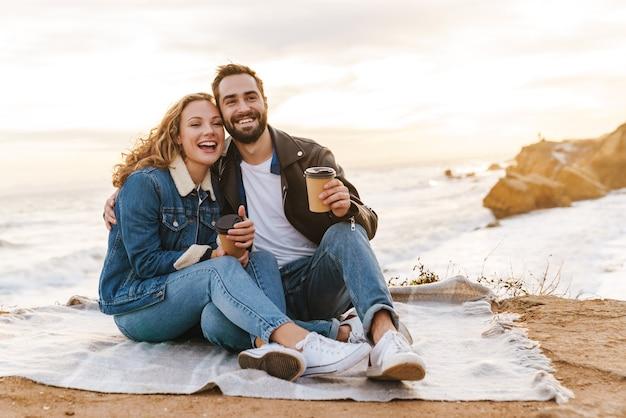 Beau jeune couple caucasien buvant du café ensemble en marchant au bord de la mer
