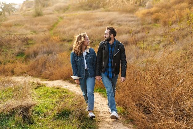 Beau jeune couple caucasien datant et marchant ensemble dans la campagne