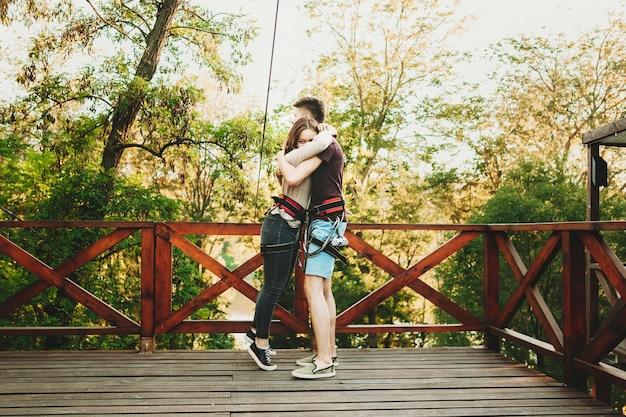 Beau jeune couple caucasien embrassant avant le sport extrême de téléphérique étant équipé tout en voyageant ensemble.
