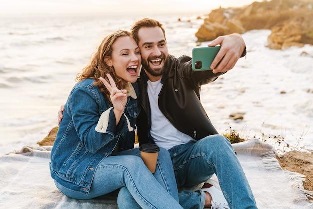 Beau jeune couple caucasien prenant une photo de selfie sur un téléphone portable en marchant au bord de la mer