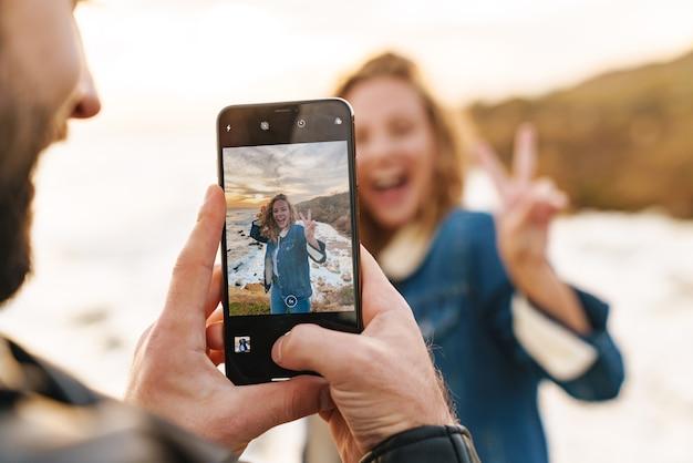 Beau jeune couple caucasien prenant une photo sur un téléphone portable en marchant au bord de la mer