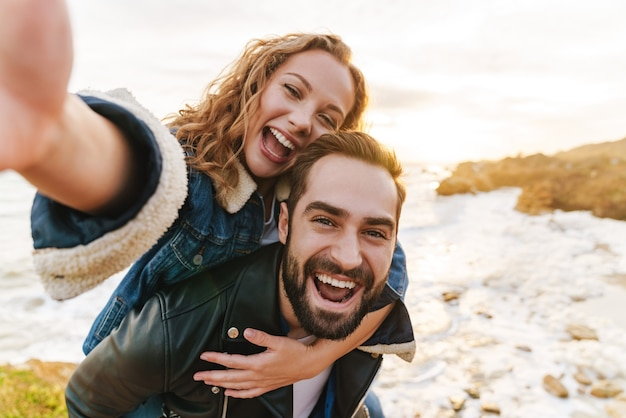 Beau jeune couple caucasien souriant et ferroutage en marchant au bord de la mer