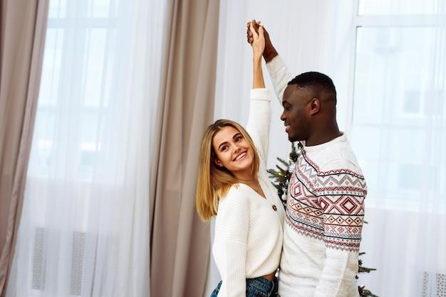 Beau jeune couple célèbre le nouvel an à la maison sur fond d'arbre de noël. heureux jeune couple dansant à noël.