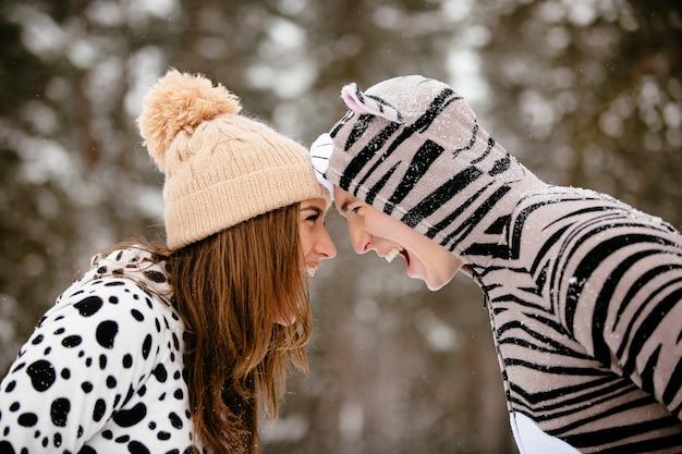 Beau jeune couple en costumes drôles passent du bon temps en hiver.