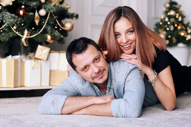 Beau jeune couple à côté de l'arbre de noël