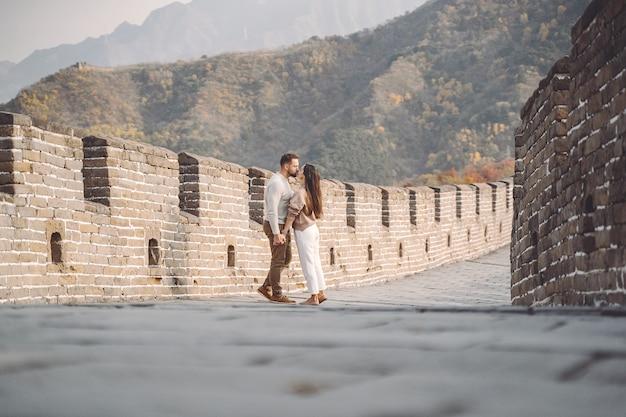 Beau jeune couple courir et sauter à la grande muraille de chine.