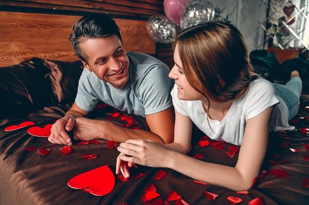 Beau jeune couple dans la chambre est allongé sur le lit. célébration de la saint-valentin.
