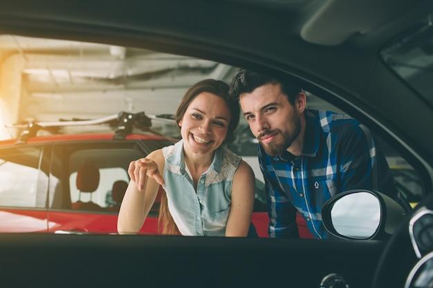 Beau jeune couple debout chez le concessionnaire en choisissant la voiture à acheter