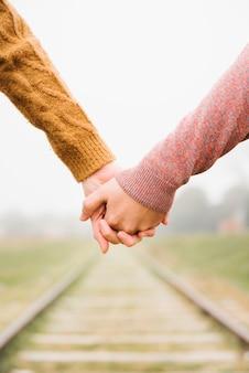 Beau, jeune couple, debout, tenant mains
