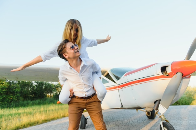 Beau jeune couple élégant en tenue officielle debout dans un avion privé