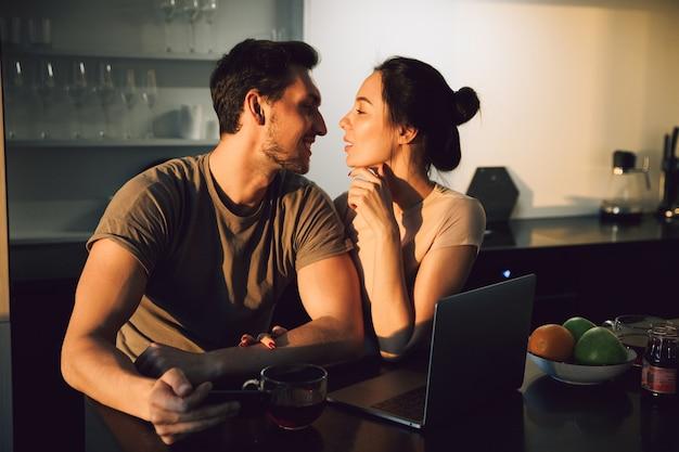 Beau jeune couple embrassant assis à la table de la cuisine avec ordinateur portable
