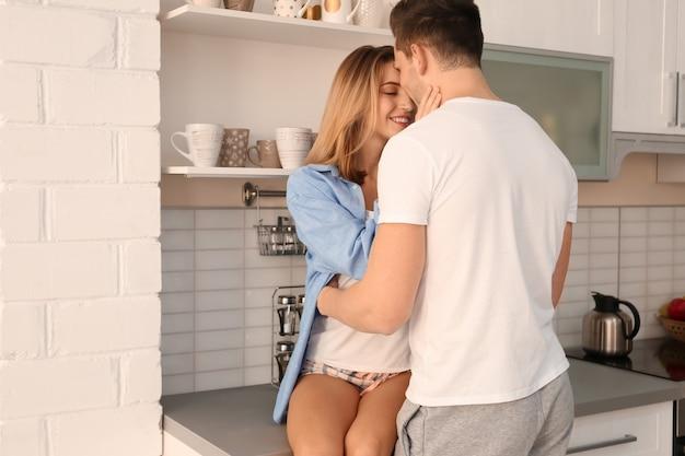 Beau jeune couple étreignant dans la cuisine