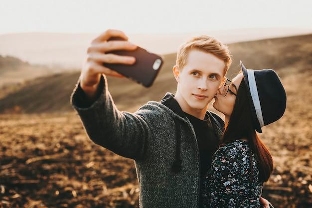 Beau jeune couple européen faisant un selfie contre une vue épique pendant que la fille embrasse son petit ami sur la joue.