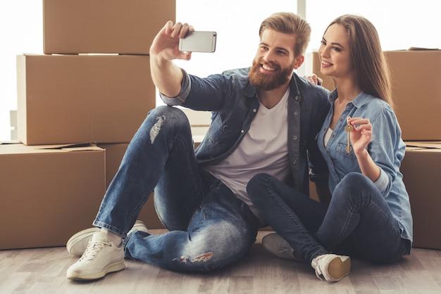 Beau jeune couple fait selfie en utilisant un smartphone
