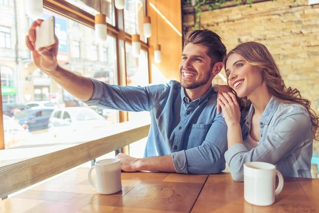 Beau jeune couple fait selfie en utilisant un smartphone.