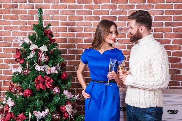 Beau jeune couple fête noël à la maison se regarder les yeux et sourire