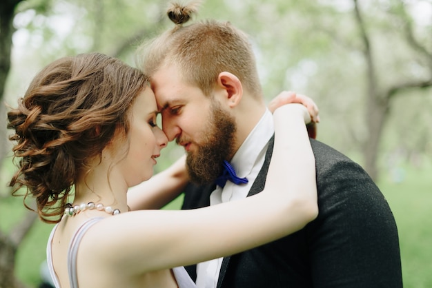 Un beau jeune couple, une fille en robe lilas et un homme en noir dans un parc d'été avec des pommiers 1