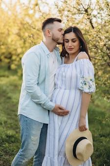 Beau jeune couple gai homme et femme enceinte en fleurs de couronne sur la tête étreignant dans le jardin d'arbre de printemps.