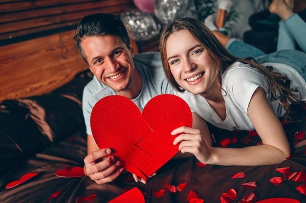 Beau jeune couple avec un grand coeur rouge dans les mains dans la chambre est allongé sur le lit et s'embrasse. célébration de la saint-valentin.