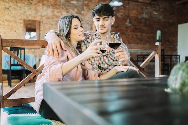 Beau jeune couple grillant avec des verres à vin.