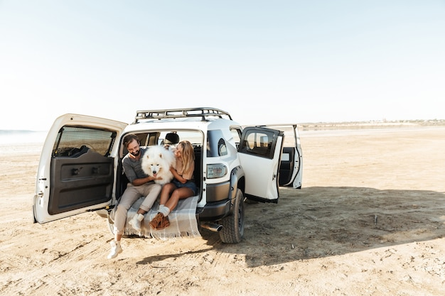Beau jeune couple heureux assis à l'arrière de leur voiture à la plage, jouant avec un chien