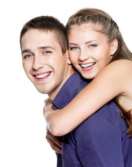 Beau jeune couple heureux sur mur blanc