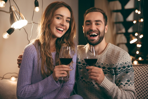 Beau jeune couple heureux, passer une soirée romantique ensemble à la maison, boire du vin rouge, griller