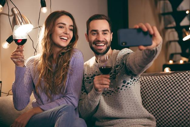 Beau jeune couple heureux, passer une soirée romantique ensemble à la maison, boire du vin rouge, prendre un selfie