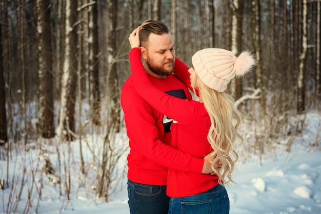 Beau jeune couple en hiver dans les bois, câlin, romance heureuse