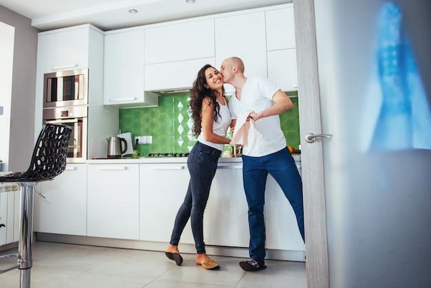 Beau jeune couple, je parle, cherche et sourit en cuisinant dans la cuisine.