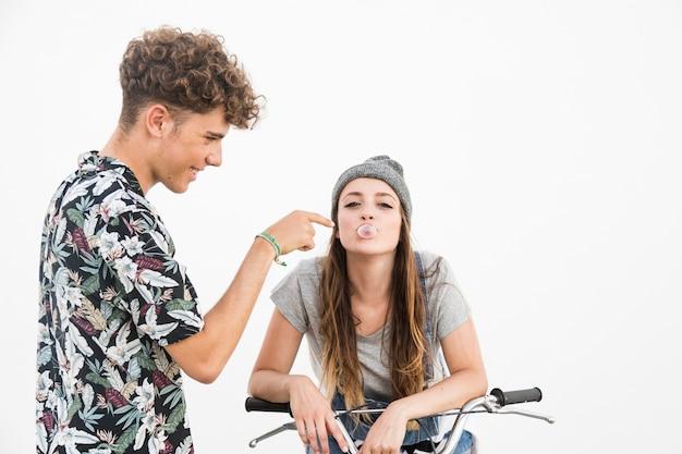 Beau jeune couple jouant avec bubble-gum sur fond blanc