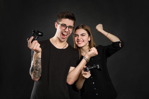 Beau jeune couple jouant à des jeux vidéo avec joysticks ensemble, isolé sur fond noir.