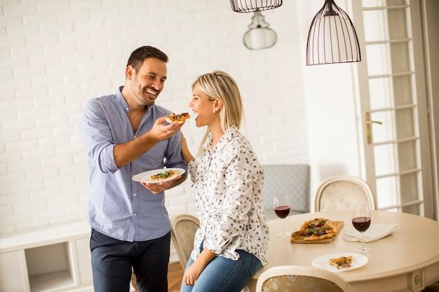 Beau jeune couple mangeant une pizza dans la chambre