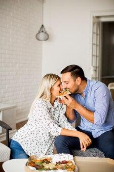 Beau jeune couple manger des pizzas dans la chambre