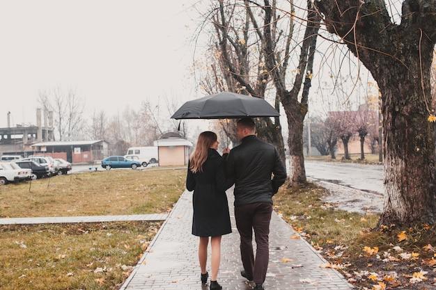 Beau jeune couple marchant sous un parapluie dans l'allée d'automne