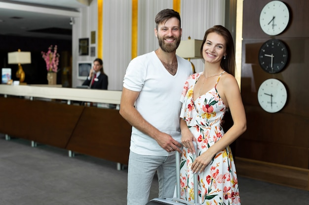 Beau jeune couple mari et femme avec valise à la réception de l'hôtel.