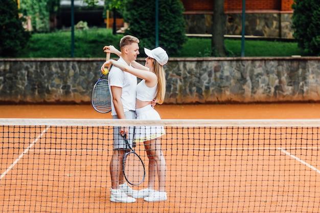 Beau jeune couple mignon joue au tennis en plein air par temps ensoleillé, fille sourit.