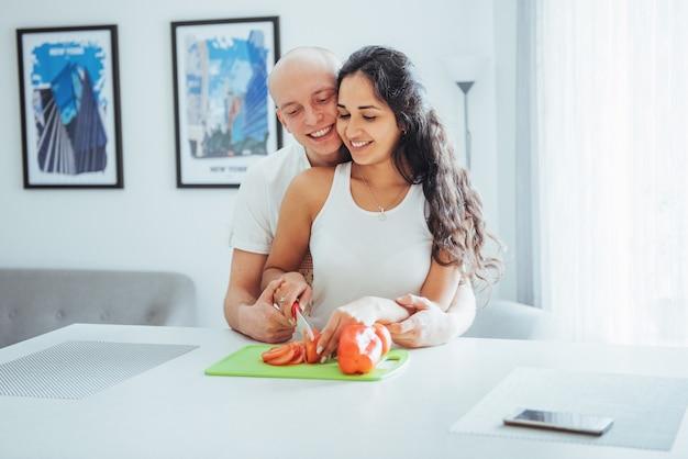 Beau jeune couple moudre les légumes ensemble dans la cuisine.