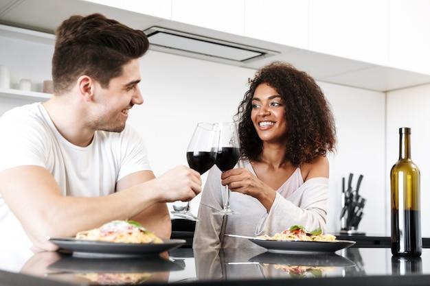 Beau jeune couple multiethnique ayant un dîner romantique à la maison, boire du vin rouge et manger des pâtes, grillage
