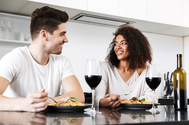 Beau jeune couple multiethnique ayant un dîner romantique à la maison, boire du vin rouge et manger des pâtes