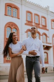 Beau jeune couple multiethnique marchant dans la rue