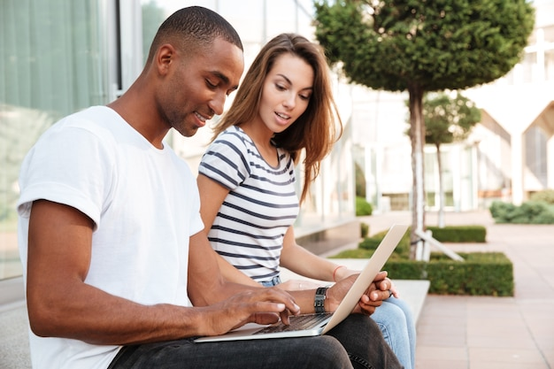 Beau jeune couple multiethnique utilisant un ordinateur portable ensemble à l'extérieur