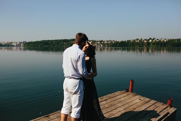 Beau jeune couple passe du temps sur la jetée en bois sur le lac