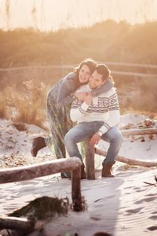 Beau jeune couple sur la plage au coucher du soleil, mise au point sélective et image tonique