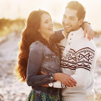 Beau jeune couple sur la plage au coucher du soleil, mise au point sélective